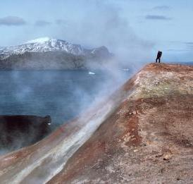 This image shows a man standing in volanic steam in Antartica.