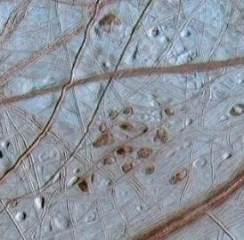 This shows Lenticulae terrain on the surface of Europa. Reddish spots and shallow pits pepper the enigmatic ridged surface of Europa in this view combining information from images taken by NASA's Galileo spacecraft during two different orbits around Jupiter.