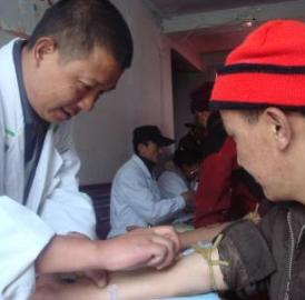 A Chinese researcher collects a blood sample from an ethnic Tibetan man participating in the DNA study.