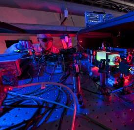 A Fermilab scientist works on the laser beams at the heart of the Holometer experiment. The Holometer will use twin laser interferometers to test whether the universe is a 2-D hologram.