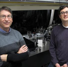 Andrew H. Marcus, left, and Mark C. Lonergan, both of the University of Oregon, stand by UO spectroscopy equipment that was adapted to study photon interactions in photocells that used lead-sulfide quantum dots as photoactive semiconductor material.