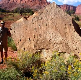 Tracy J. Thomson stands next to a block with numerous swim tracks in Capitol Reef National Park, Utah.