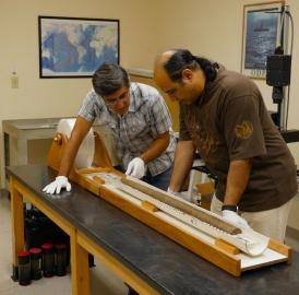 Ali Pourmand (left) and Ph.D. candidate Arash Sharifi visually inspect the physical properties of a sediment core collected from NW Iran. This meter-long core recorded the environmental condition of the region for the past 2000 years.