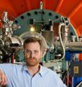 """Darryl Granger, a Purdue professor of earth and atmospheric sciences, stands with the accelerator mass spectrometer used in a study that determined the age of """"Peking Man"""" was around 200,000 years older than previously thought. Purdue is the only university in the nation with an accelerator mass spectrometer powerful enough to perform the type of testing used in this study."""