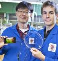 Jeong-Yun Sun (left) and Christoph Keplinger (right), Harvard University, demonstrate their transparent ionic speaker. It uses a signal conducted by ions, rather than electrons, to vibrate a rubber membrane.