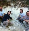 Left to right, Biaggio Giaccio, Gianluca Sotilli, Courtney Sprain and Sebastien Nomade sitting next to an outcrop in the Sulmona basin of the Apennines that contains the Matuyama-Brunhes magnetic reversal. A layer of volcanic ash interbedded with the lake sediments can be seen above their heads.