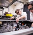 SLAC researchers Michael Litos, left, and Sebastien Corde use a laser table at the Facility for Advanced Accelerator Experimental Tests (FACET) to create a plasma used for accelerating electrons to high energies in a very short distance.