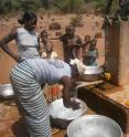 This image shows women collecting water at a well in rural Burkina Faso, West Africa.