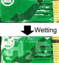 A coating on a circuit board is unobservable when dry (top) but wrinkles to display 'H<sub>2</sub>O' when exposed to moisture (bottom).