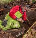 Dave McMahan, Neva Project principal investigator, takes notes in a completed excavation block.
